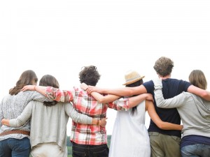 Rear view of group of friends hugging. Horizontal.